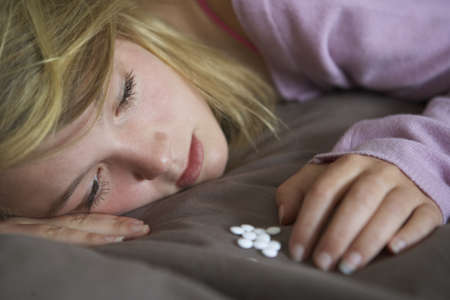drug addiction: Depressed Teenage Girl Sitting In Bedroom With Pills Stock Photo
