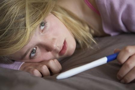 prueba de embarazo: Adolescente deprimida, sentado en el dormitorio con prueba de embarazo Foto de archivo