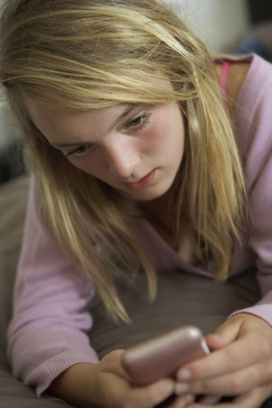 Unhappy Teenage Girl Lying In Bedroom With Mobile Phone photo