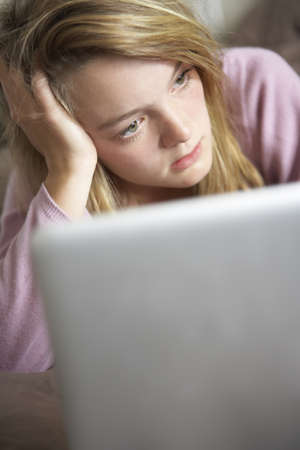 Unhappy Teenage Girl Using Laptop At Home Stock Photo - 9875783