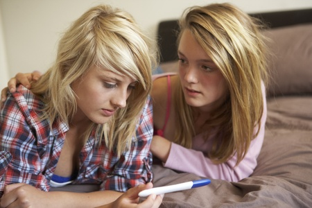 pregnancy: Two Teenage Girls Lying On Bed Looking At Pregnancy Testing Kit