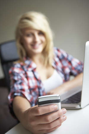 Teenage Girl Using Laptop And Mobile At Home photo