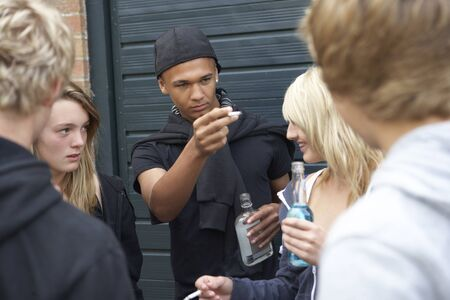 intimidating: Group Of Threatening Teenagers Hanging Out Together Outside Drinking