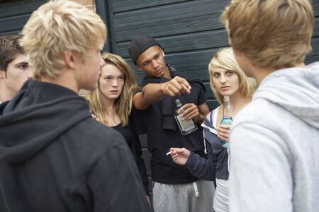gang: Group Of Threatening Teenagers Hanging Out Together Outside Drinking
