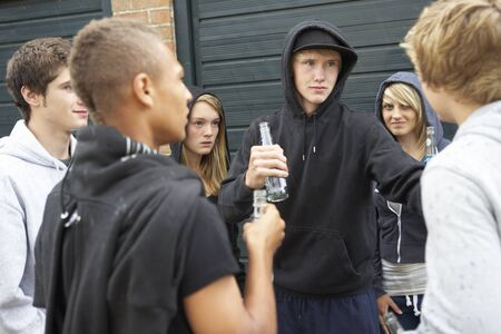 bully: Group Of Threatening Teenagers Hanging Out Together Outside Drinking