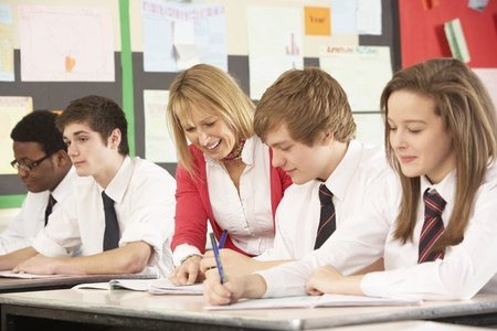 uniform student: Teenage Students Studying In Classroom With Teacher Stock Photo