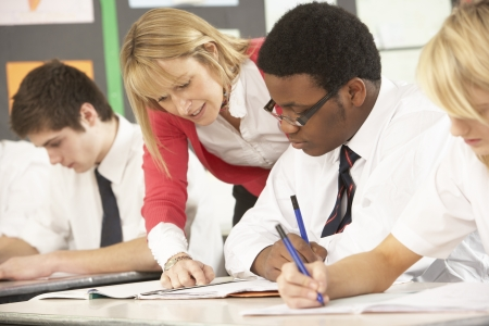 secondary education: Teenage Students Studying In Classroom With Teacher Stock Photo