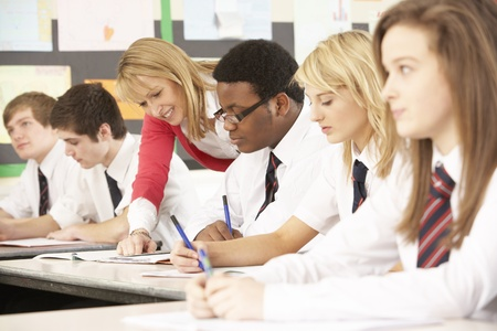 secondary schools: Teenage Students Studying In Classroom With Teacher Stock Photo