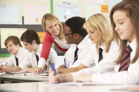 secondary school: Teenage Students Studying In Classroom With Teacher Stock Photo