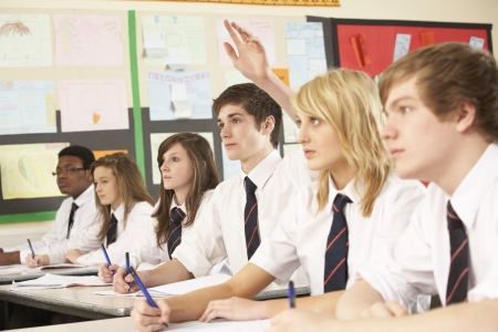 uniform school: Estudiante adolescente responder a pregunta estudiando en aula Foto de archivo