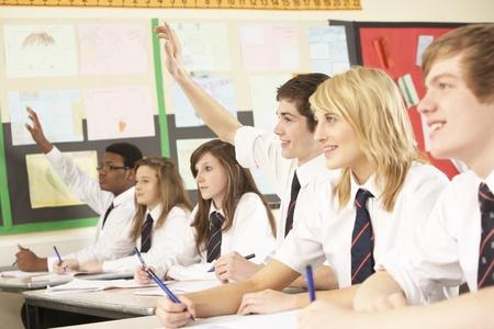 Adolescenti studente di rispondere alla domanda studiando In aula Archivio Fotografico