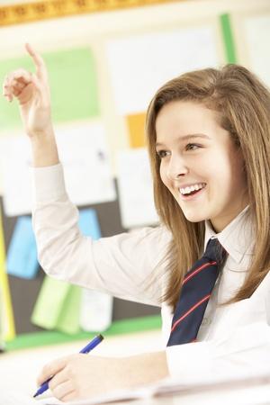 school children uniform: Teenage Female Student Answering Question In Classroom