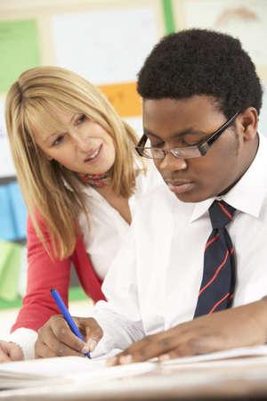 tutor: Estudiante adolescente de trabajo en el aula con profesor Foto de archivo
