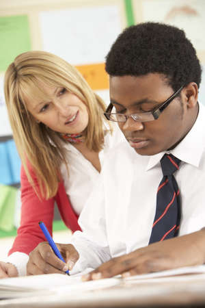 Teenage Student Working In Classroom With Teacher photo