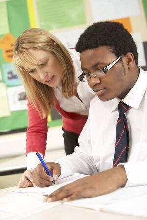 tutor: Teenage Student Working In Classroom With Teacher
