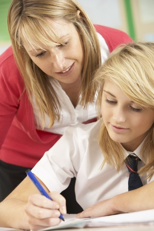 uniform student: Female Teenage Student Studying In Classroom With Teacher Stock Photo