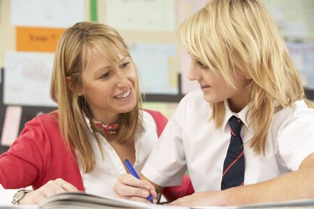 Mujer adolescente estudiante en el aula con el profesor