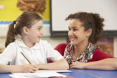 school uniform girl: Schoolgirl Studying In Classroom With Teacher