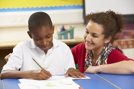 junior education: Schoolboy Studying In Classroom With Teacher Stock Photo