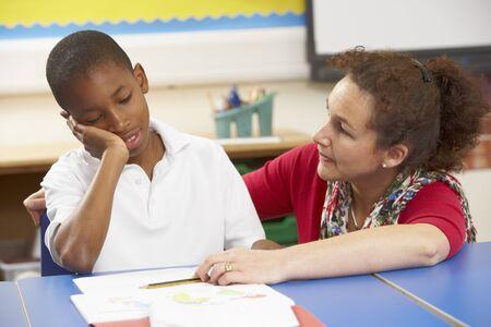 Infeliz colegial estudiando en el aula con el profesor