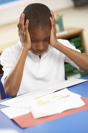 nine years old: Stressed Schoolboy Studying In Classroom