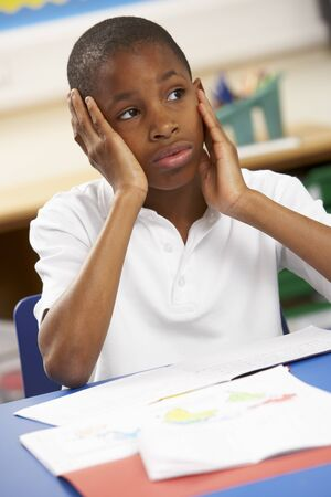 Unhappy Schoolboy Studying In Classroom Stock Photo - 9910970