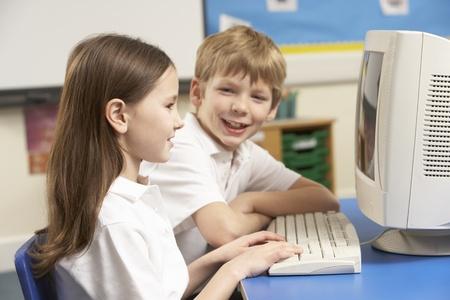 junior education: Schoolchildren In IT Class Using Computer Stock Photo