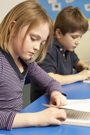 Schoolgirl Reading Book In Classroom Stock Photo