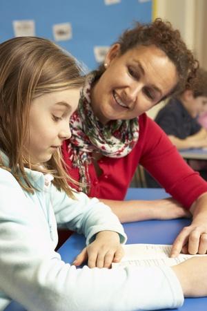 non uniform: Schoolgirl Studying In Classroom With Teacher