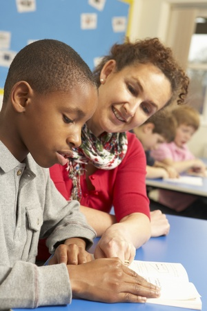 non uniform: Schoolboy Studying In Classroom With Teacher Stock Photo