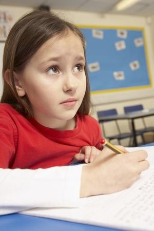 upset: Stressed Schoolgirl Studying In Classroom