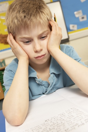 eight year old: Stressed Schoolboy Studying In Classroom