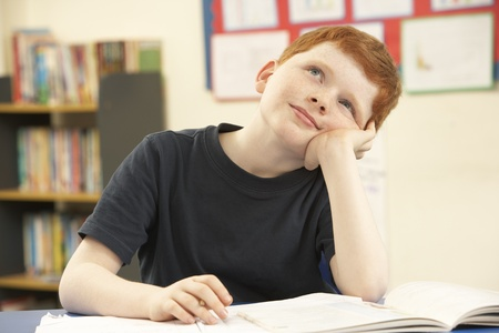 daydreaming: Schoolboy Daydreaming In Classroom Stock Photo