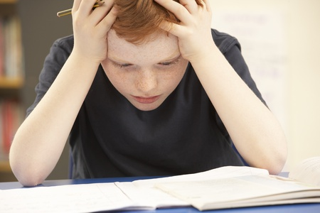 struggling: Stressed Schoolboy Studying In Classroom