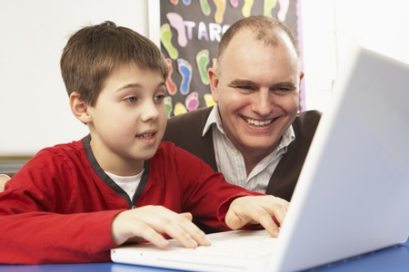 nine year old: Schoolboy In IT Class Using Computer With Teacher