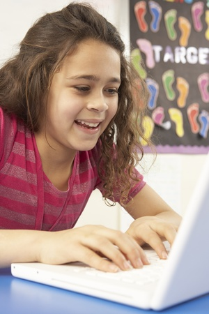 nine year old: Schoolgirl In IT Class Using Computer With Teacher Stock Photo