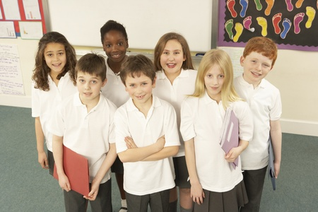 UNIFORM: Portrait Of Schoolchildren Standing In Classroom