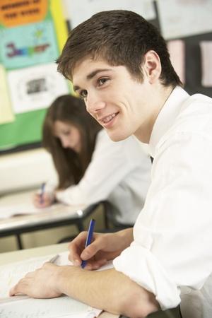 uniform school: Estudiante adolescente masculino Estudiar en el aula