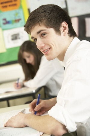 secondary school: Male Teenage Student Studying In Classroom Stock Photo