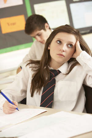 Bored Female Teenage Student Studying In Classroom photo
