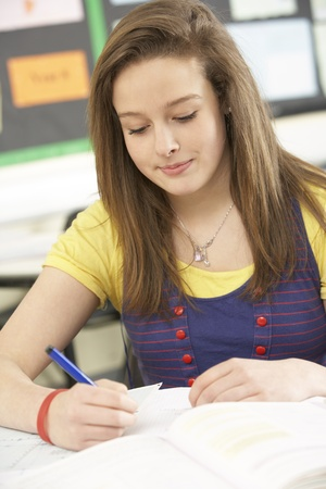 non uniform: Female Teenage Student Studying In Classroom