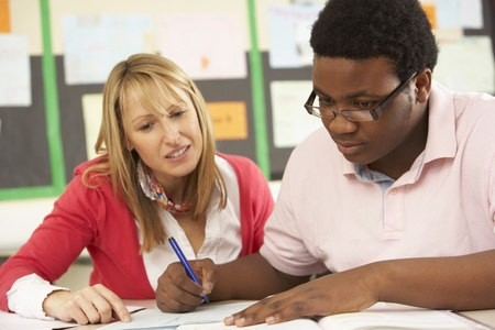 Male Teenage Student Studying In Classroom With Teacher Stock Photo - 9911027