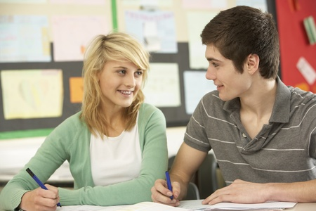 Male And Female Teenage Students Studying In Classroom photo