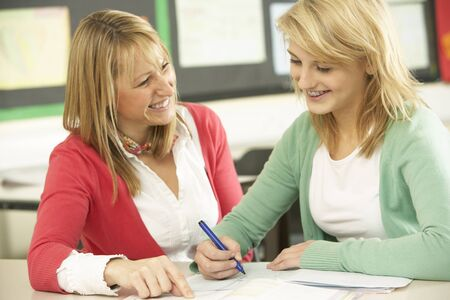 non uniform: Female Teenage Student Studying In Classroom With Teacher Stock Photo