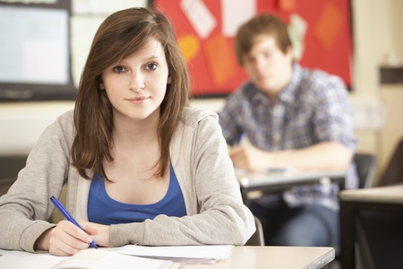 Female Teenage Student Studying In Classroom photo