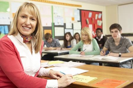 secondary school teacher: Teenage Students Studying In Classroom With Teacher Stock Photo