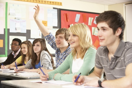 concentrating: Teenage Students Studying In Classroom Answering Question