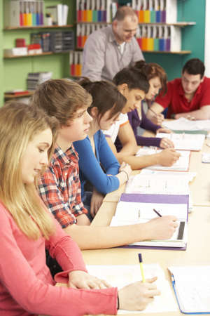 Teenage Students Studying In Classroom With Tutor photo