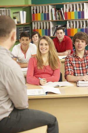 lecturing: Teenage Students Studying In Classroom With Tutor Stock Photo