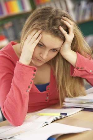 Stressed Female Teenage Student Studying In Classroom photo